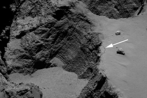 Image of the Aswan cliff. The white arrow shows the 70m long, 1m wide fracture at the edge of the cliff © ESA/Rosetta/MPS for OSIRIS Team MPS/UPD/LAM/IAA/SSO/INTA/UPM/DASP/IDA
