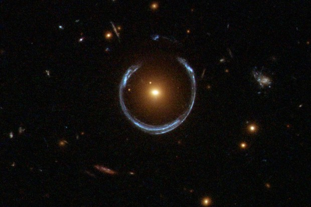 The gravity of a luminous red galaxy has gravitationally distorted the light from a much more distant blue galaxy. NASA/ESA