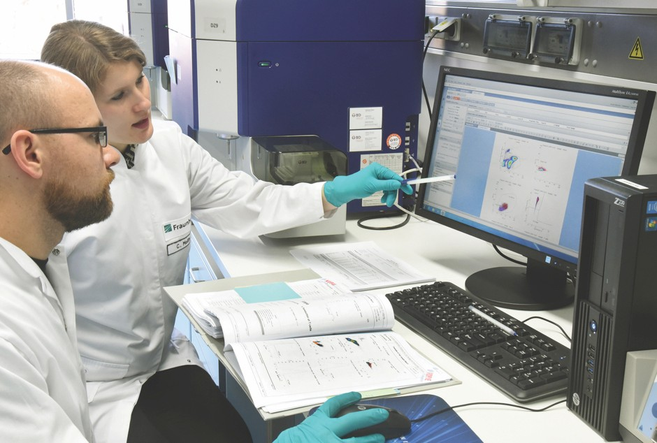 At the Fraunhofer Institute in Germany, biochemist Christin Meiẞner (right) and medical technical assistant Andreas Kirschner analyse cells for a new form of cancer therapy © Alamy