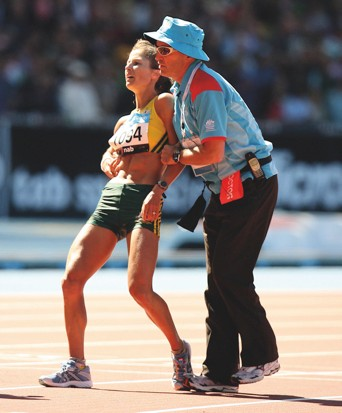 Kate Smyth was escorted from the track when she collapsed after running the marathon at the 2006 Commonwealth Games © Getty Images