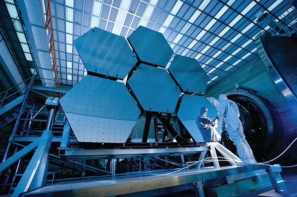Engineers work on the mirror of the James Webb Space Telescope (JWST)