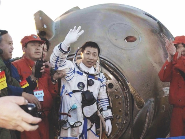 Yang Liwei, the first Chinese astronaut (also called a taikonaut), waves to the crowds after stepping out of the Shenzhou-5 re-entry capsule in October 2003 © Getty Images