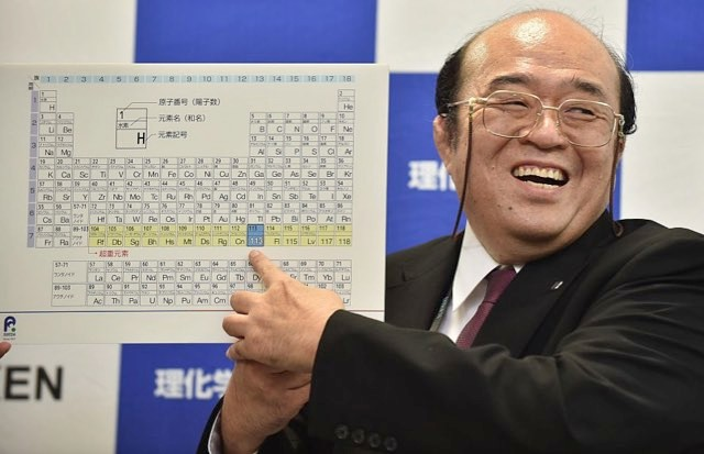 Kosuke Morita smiles as he points to a board displaying the new atomic element 113 during a press conference © Kazuhiro Nogi/AFP/Getty Images