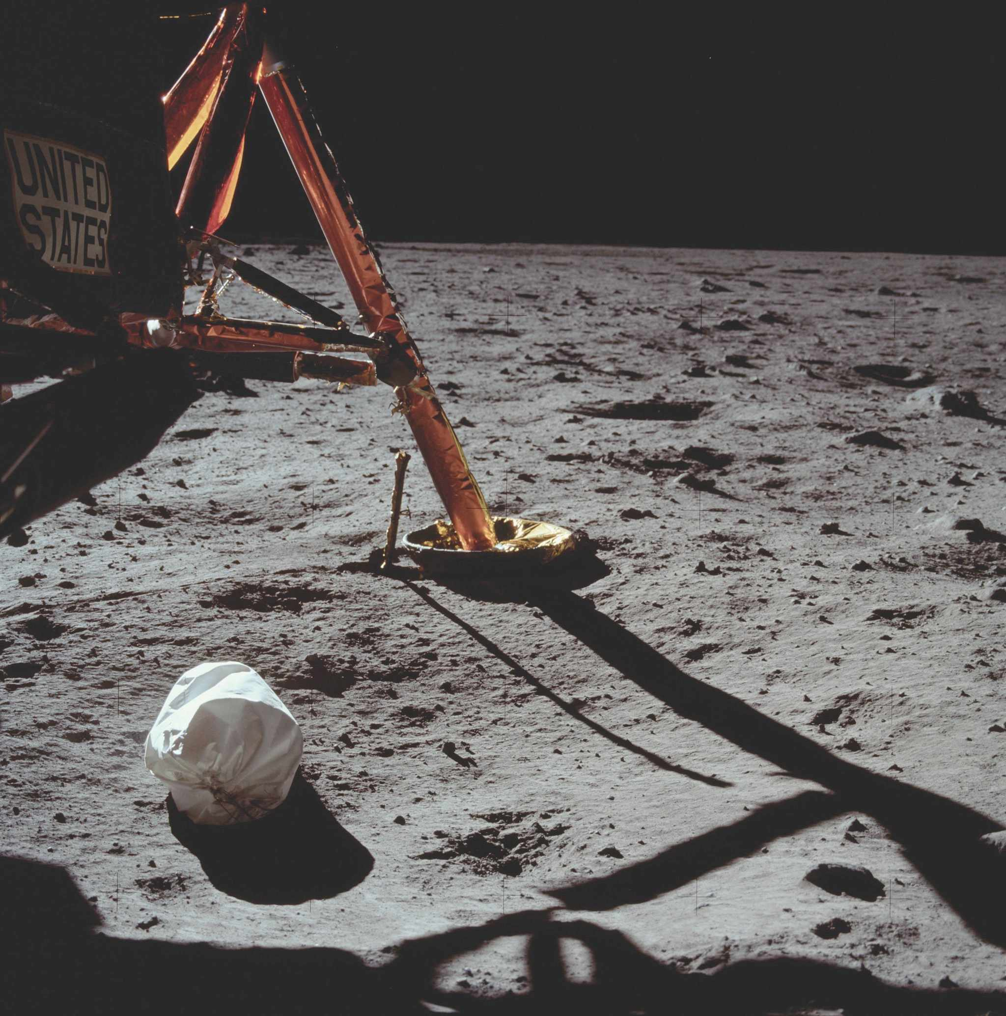 Armstrong's first photograph on the lunar surface, taken 23 minutes into the moonwalk, shows Eagle's footpad and strut support, plus a white jettison bag full of rubbish from the lunar module. The bag was left on the surface to free up space in the cramped cabin. © NASA/JPL