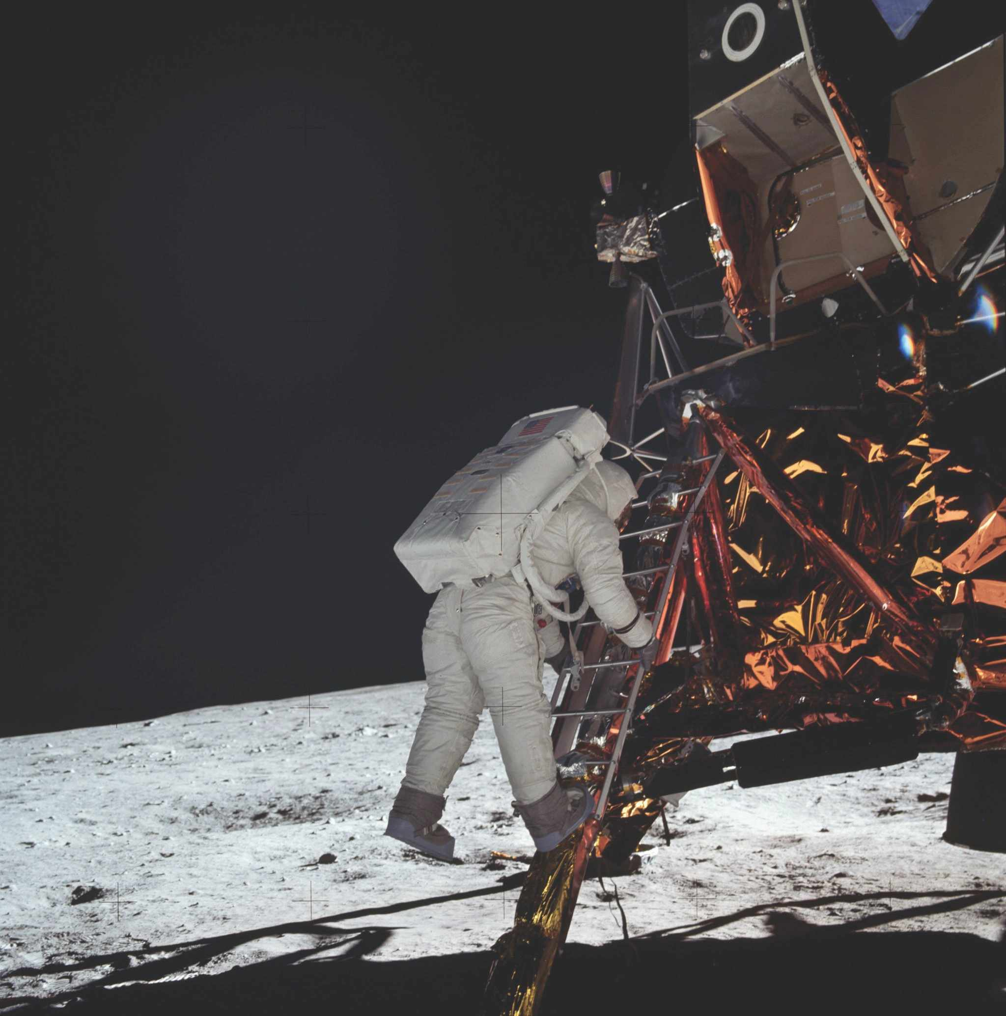 Half an hour after stepping out of the lunar module, Armstrong captures shots of his crew-mate Aldrin making the same feet-first exit onto the Moon. It takes Aldrin three minutes to make it to the bottom of the lunar module's ladder. © NASA/JPL