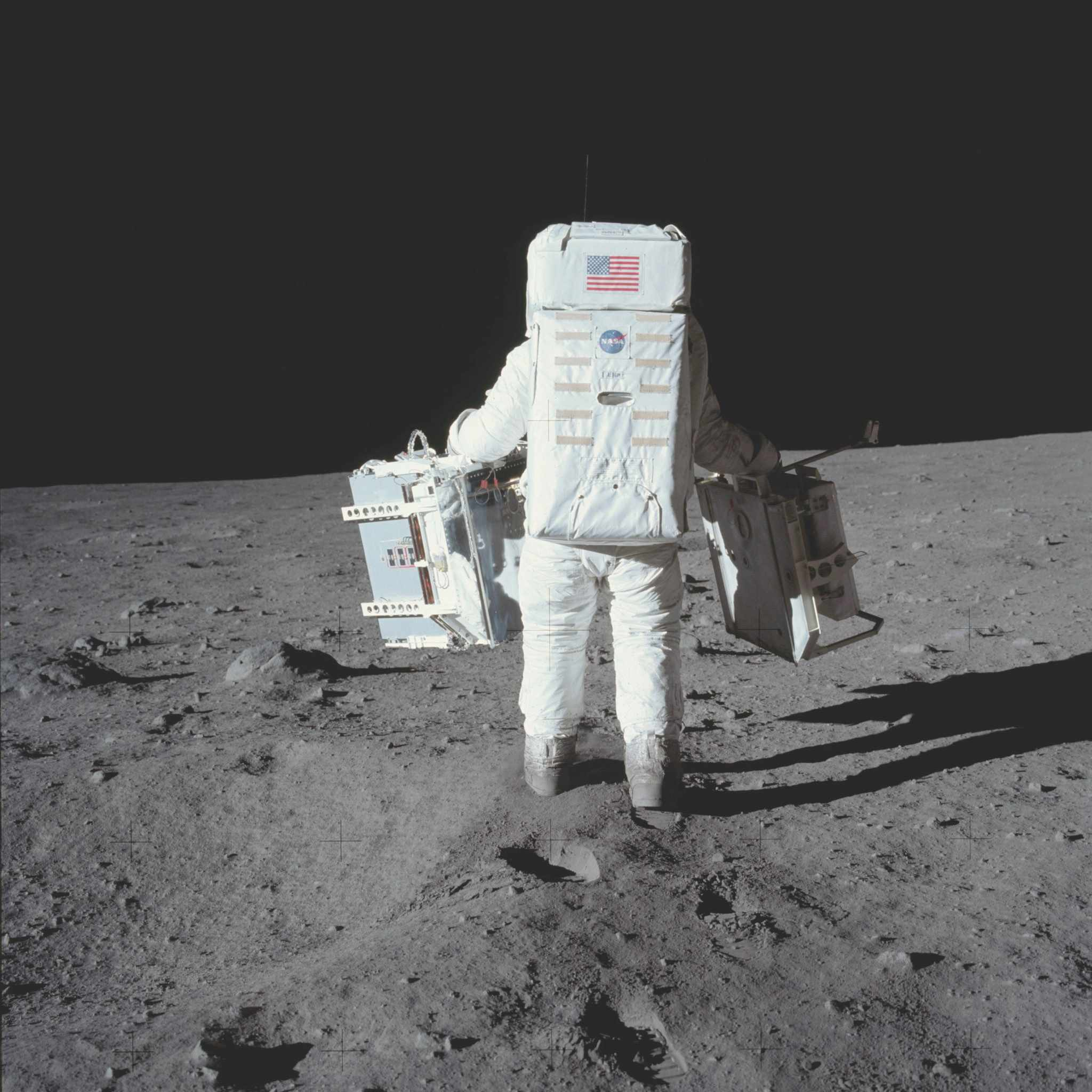 Reduced lunar gravity makes it easy for Aldrin to carry a pair of experiment packages for deployment © NASA/JPL