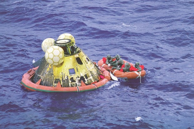 24 July 1969 Half an hour after 'landing', the Apollo 11 crew, dressed in isolation suits, are met and extracted by a navy diver before being airlifted to the USS Hornet (above). © NASA/JSC
