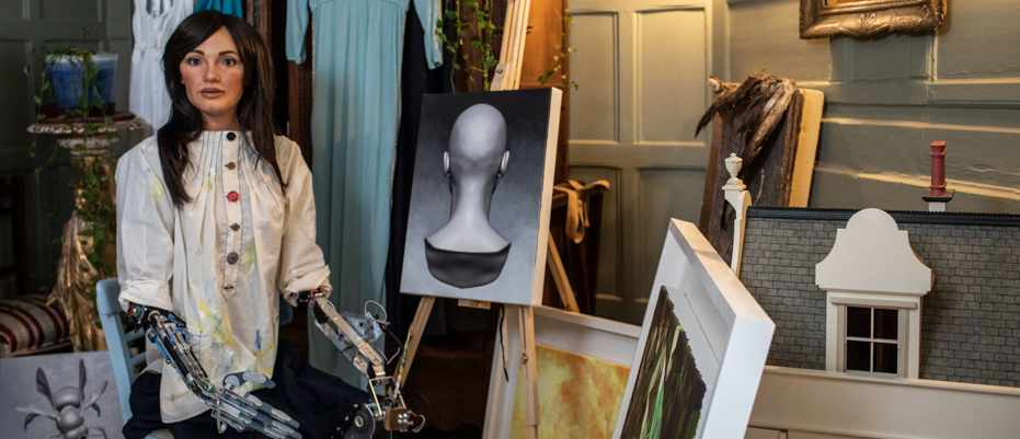 Ai-Da, a realistic humanoid robot, with the art she has painted © Shutterstock