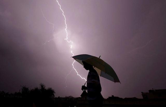 A pedestrian walks with an umbrella as lightning strikes during an evening thunderstorm in Jammu on May 14, 2015. AFP PHOTO / RAKESH BAKSHI / AFP / rakesh bakshi (Photo credit should read RAKESH BAKSHI/AFP/Getty Images)