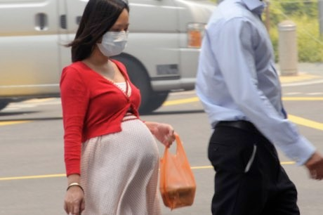 Black carbon from air pollution 'found on the baby's side of the placenta' (A pregnant woman with a face mask walking on the street in Singapore ©Rahman/AFP/Getty Images)