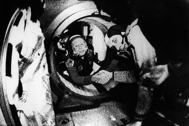 Commander of the Soviet crew of Soyuz, Alexei Leonov (L) and commander of the American crew of Apollo, Thomas Stafford (R), shake hands 17 July 1975 in the space, somewhere over Western Germany, after the Apollo-Soyuz docking manoeuvres © AFP/AFP/Getty Images