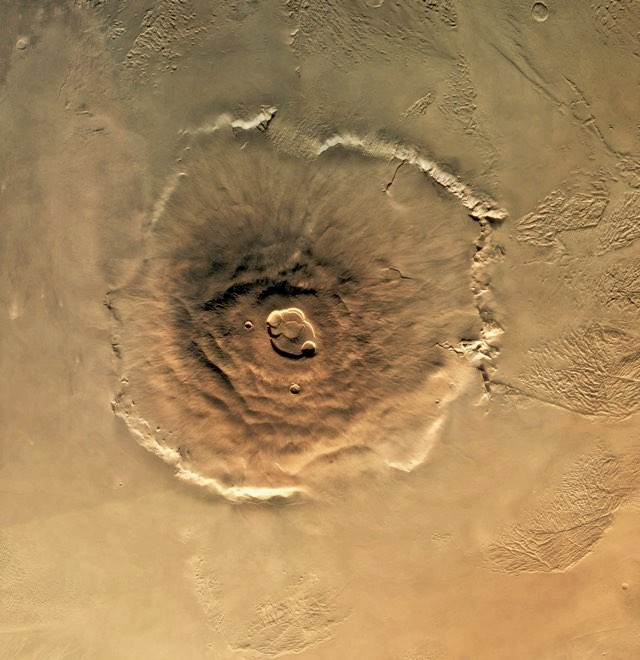 A Viking Orbiter/Lander spacecraft photographed this view of Olympus Mons, the largest volcano in the solar system. It rises 90,000 feet above the surface and is as big as Arizona. | View from: Viking Orbiter/Lander. © Getty Images