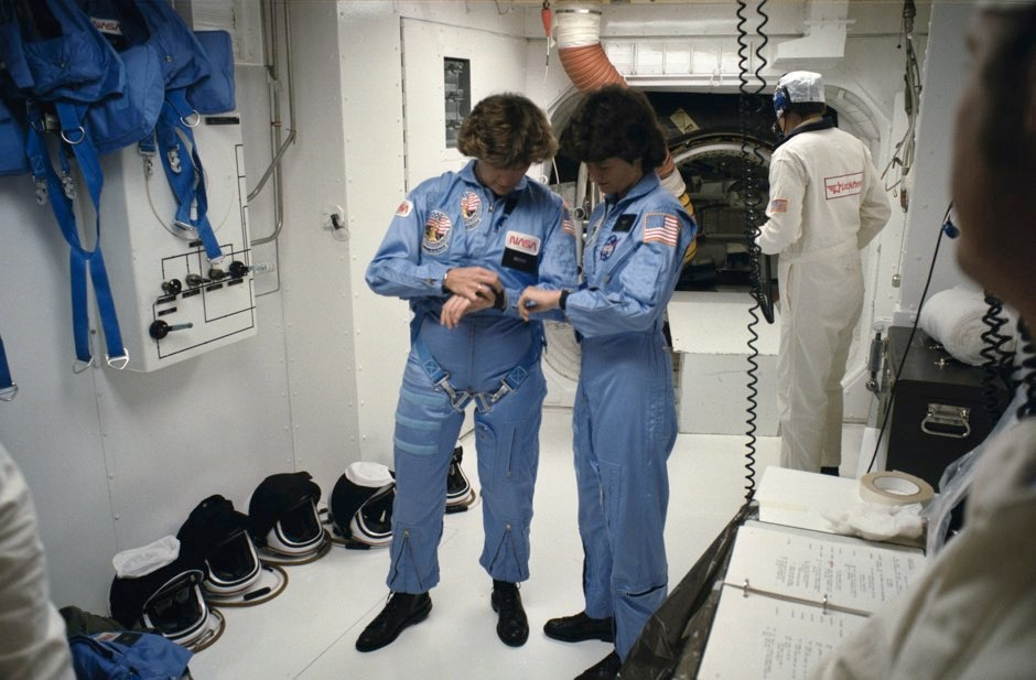 "Sally Ride, right, and astronaut Kathryn Sullivan synchronize their watches in the ""white room"" before entering the shuttle Challenger to launch on mission STS-41G on October 5, 1984 © NASA"