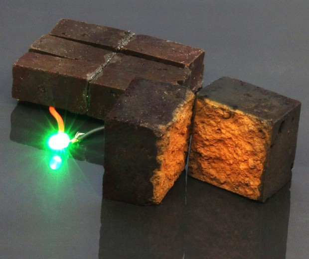 Red brick device developed by chemists at Washington University in St. Louis lights up a green light-emitting diode (D'Arcy laboratory: Washington University in St. Louis)