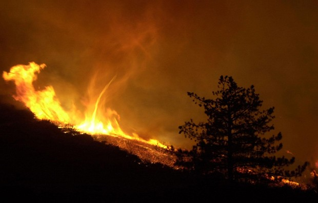 A large tornado of fire swirls on a mountain side in the Anza-Borrego Desert State Park near Anza, CA, USA