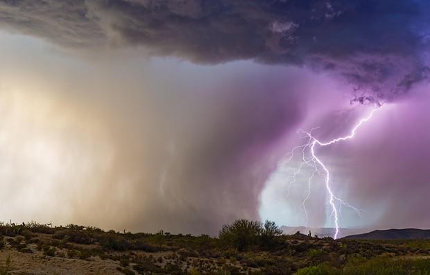 Lightning strikes beside a powerful microburst from a monsoon thunderstorm near Florence, Arizona.