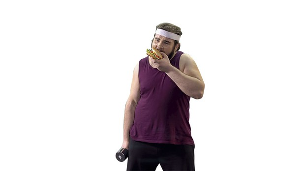 A man in workout clothes eating a burger © Getty Images