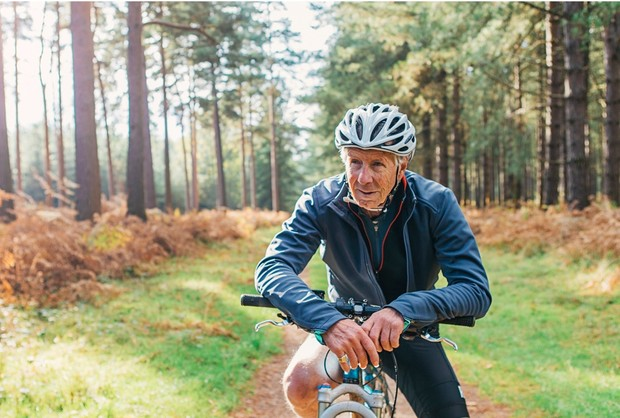 Senior man on a bicycle in the forest