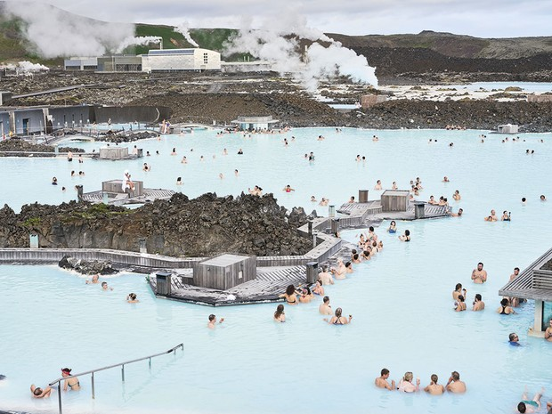 A large group of people relaxing in a pale blue lagoon © Luca Locatelli/Institute