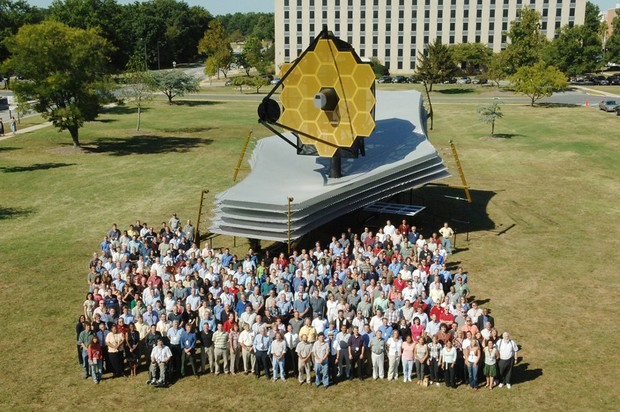 Los empleados de la NASA se paran junto a una réplica a tamaño real del telescopio James Webb © NASA