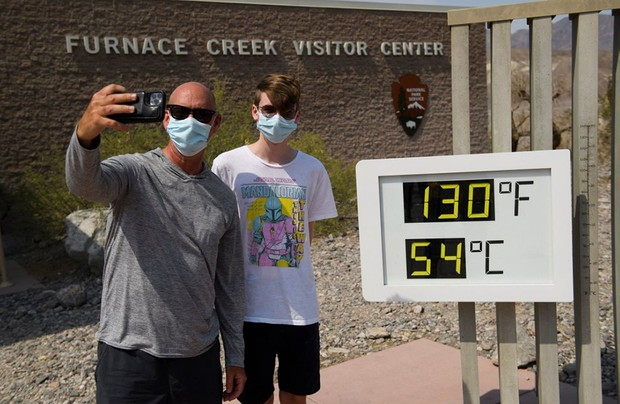 Tourists on a road trip from Texas, take pictures with a thermometer displaying temperatures of 130 Degrees Fahrenheit (54 Degrees Celsius) at the Furnace Creek Visitor's Center at Death Valley National Park in June 17, 2021. - Much of the western United States is braced for record heat waves this week, with approximately 50 million Americans placed on alert Tuesday for