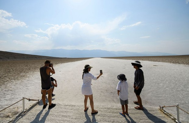 Visitors take pictures at the salt flats of Badwater Basin inside Death Valley National Park on June 17, 2021 in Inyo County, California. - Much of the western United States is braced for record heat waves this week, with approximately 50 million Americans placed on alert on June 15 for