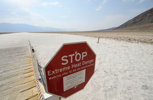 TOPSHOT - Signage warns of extreme heat danger at the salt flats of Badwater Basin inside Death Valley National Park on June 17, 2021 in Inyo County, California. - Much of the western United States is braced for record heat waves this week, with approximately 50 million Americans placed on alert on June 15 for
