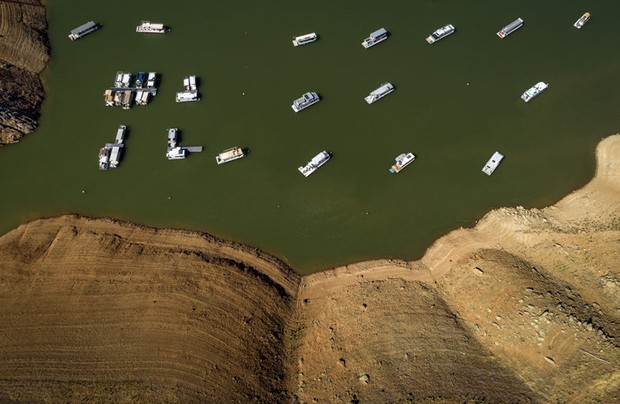 OROVILLE, CA - JUNE 08: In an aerial view, houseboats whose owners chose to leave them in the lake, float near the lake's shore at the Lime Saddle Marina for Lake Oroville near Paradise, Calif., on Tuesday, June 8, 2021. Drought has caused the water level to drop in Lake Oroville several hundred feet, leaving houseboat owners to make a choice to leave their craft in the water or to remove them since boat ramps will not reach the low level of the water as it drops lower and lower. (Carlos Avila Gonzalez / The San Francisco Chronicle via Getty Images)