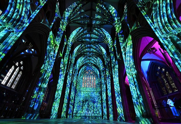 The interior of Lichfield Cathedral is bathed in colourful patterns of light during The Great Exhibition : Science light and sound projection show in Lichfield, central England, on August 24, 2021. - 'The Great Exhibition : Science light and sound show which opening at Lichfield Cathedral sees the inside of the 900 year old Cathedral bathed in moving light and sound projections that explore the world of science, and the ways in which it has shaped our past as well as considering how it will influence our future. (Photo by Paul ELLIS / AFP) (Photo by PAUL ELLIS/AFP via Getty Images)