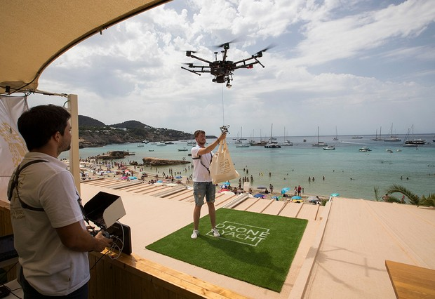 A drone pilot ties up a bag of food to a drone at Cala Tadira near Sant Josep de Sa Talaia in Ibiza Island on August 24, 2021. Drone to Yacht is an exclusive delivery service for yachts launched in Ibiza by the restaurant Can Yucas and the Galician company Aerocamaras to deliver food and drinks to yachts. (Photo by JAIME REINA / AFP) (Photo by JAIME REINA/AFP via Getty Images)
