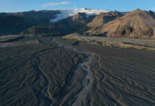 In this aerial view, meltwater descends in shifting rivulets from Vatnajokull ice cap on August 14, 2021 near Hof, Iceland. Iceland is undergoing a strong impact from global warming. Since the 1990s 90% of Iceland's glaciers have been retreating and projections for the future show a continued and strong reduction in size of its three ice caps. Fjallsjokull is one of dozens of glacier tongues that descend from Vatnajokull, Iceland's biggest ice cap, along Iceland's southeastern coast. (Photo by Sean Gallup/Getty Images)