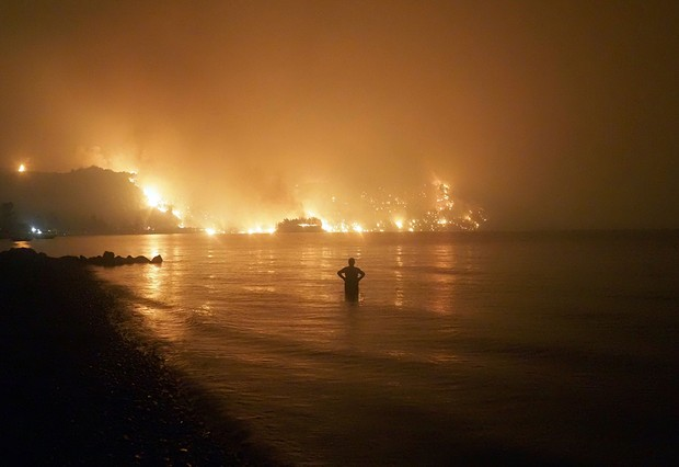 Photo by Thodoris Nikolaou/AP/Shutterstock (12253990a) Dated, a man watches as wildfires approach Kochyli beach near Limni village on the island of Evia, about 160 kilometers (100 miles) north of Athens, Greece. A new massive United Nations science report is scheduled for release Monday Aug. 9, 2021, reporting on the impact of global warming due to humans UN Climate Report, Limni, Greece - 06 Aug 2021