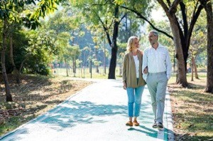 Senior citizen couple taking a walking in a park during summer morning. Seniors couple spend time in public park together.