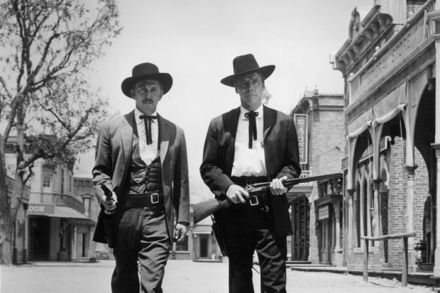 Kirk Douglas And Burt Lancaster walk with gun drawn in a scene from the film 'Gunfight At The O.K. Corral', 1957. (Photo by Paramount Pictres/Getty Images)