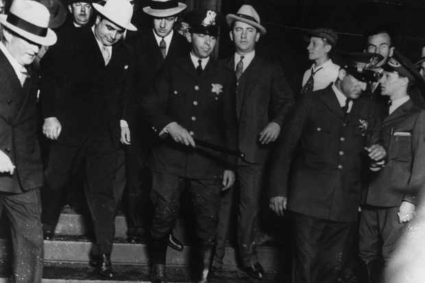 Capone (in the plain white hat) leaves court after being found guilty in 1931. As well as receiving a prison sentence, he was also made to pay his taxes. (Image by Alamy)