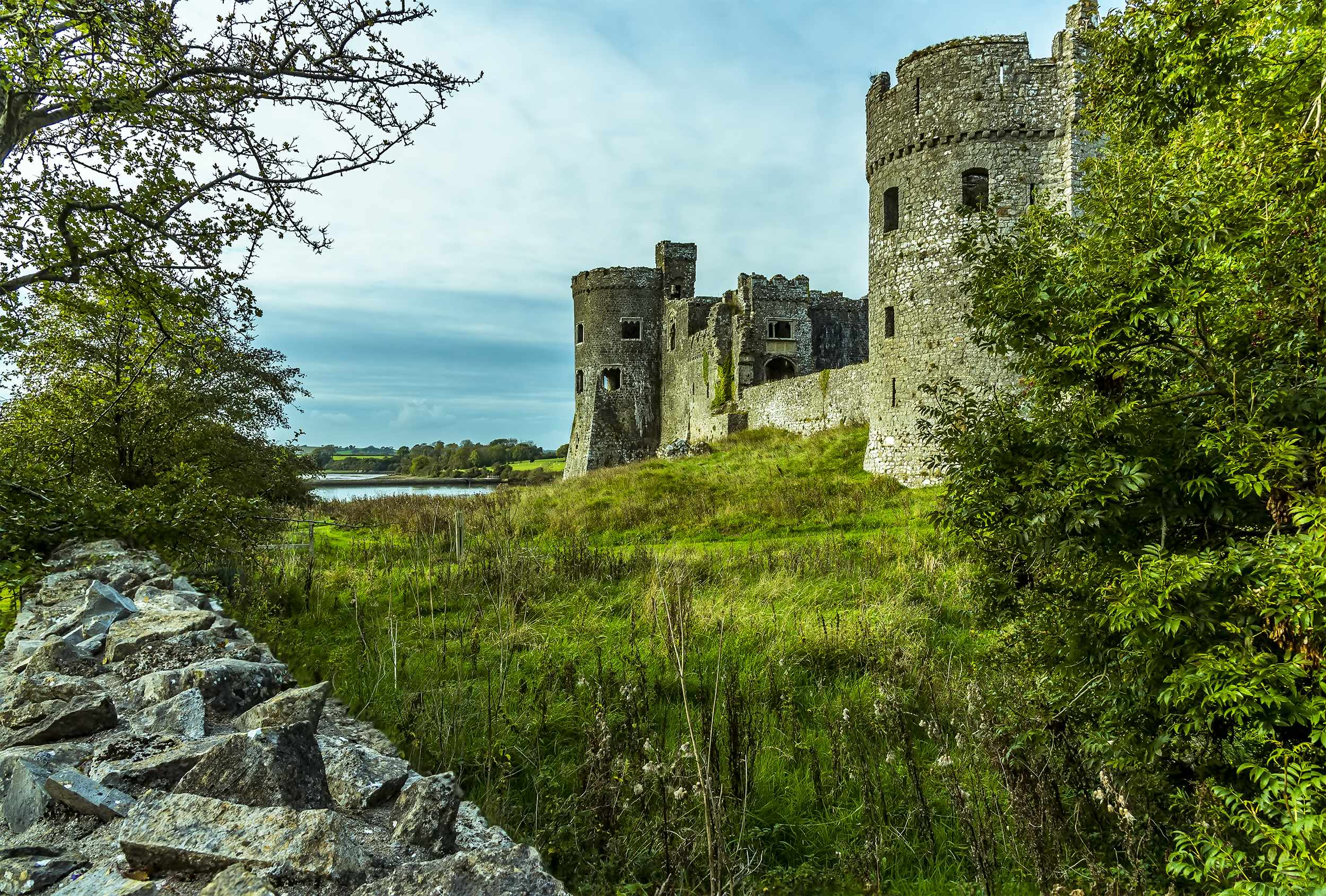 A view towards the Carew estuary between a dry stone wall and the ruins of Carew Castle, Pembrokeshire, UK. (Dreamstime)