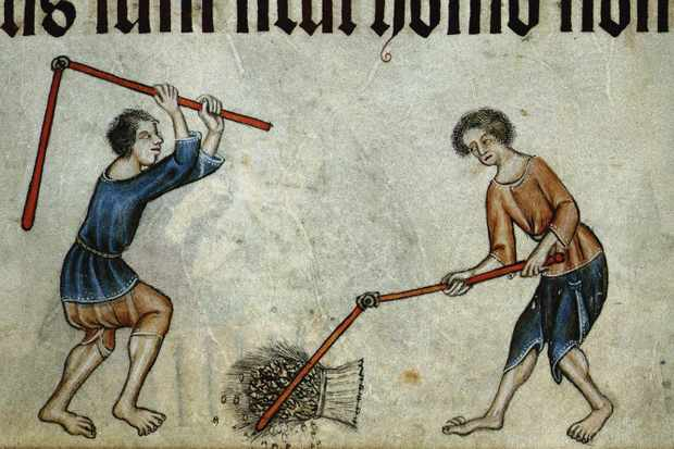 Two medieval men thresh a sheaf of wheat in this 14th century illustration. (Photo by Fine Art Images/Heritage Images/Getty Images)