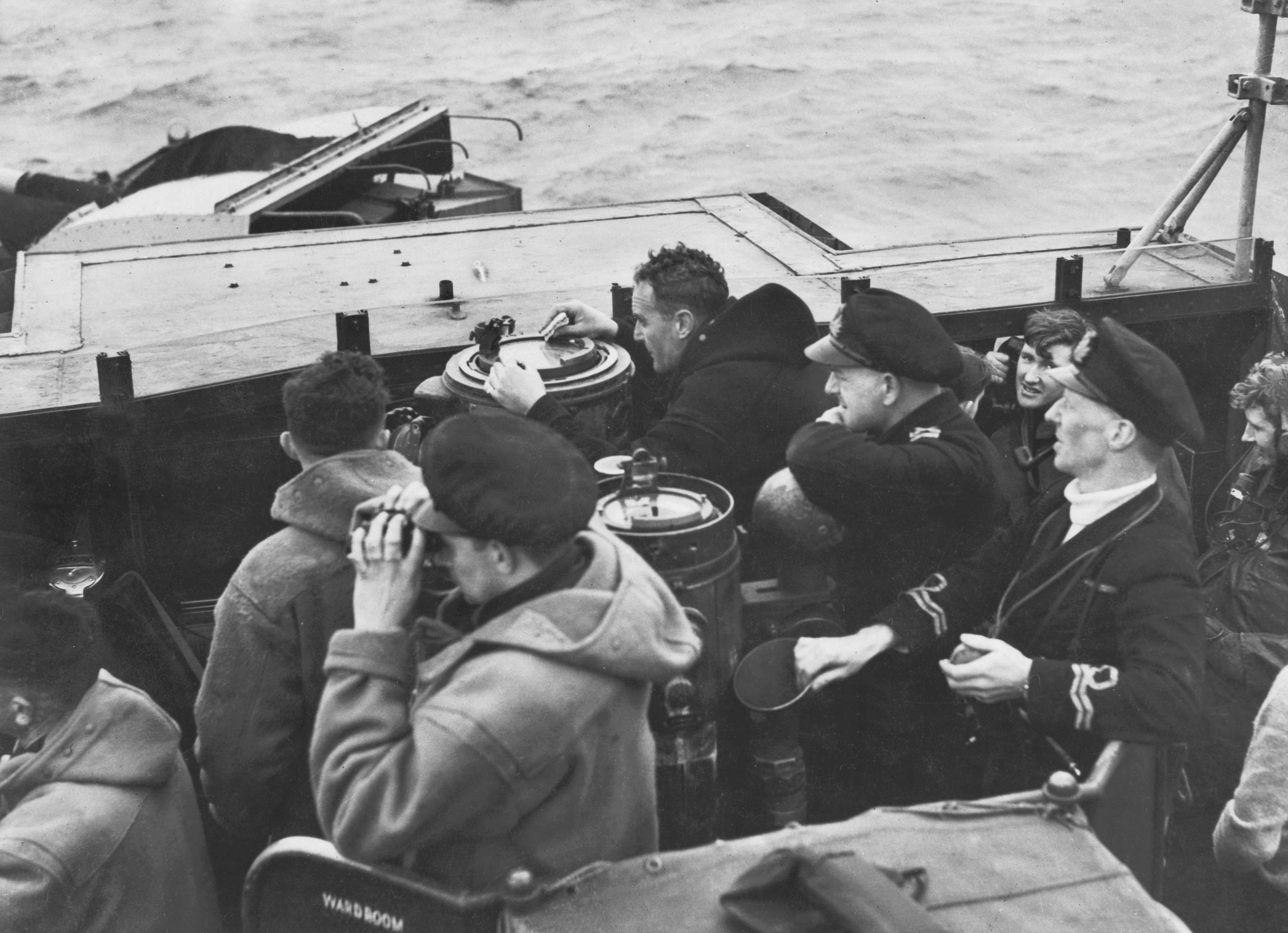Captain Walker (fourth from the left), clutching a hastily grabbed sandwich in his right hand, plots his next move during a patrol that saw his group notch up a record six kills, February 1944. (Photo by Past Pix/SSPL/Getty Images)