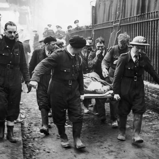A woman is carried away on a stretcher following a German bombing raid on London, c1940. (Photo by Fox Photos/Hulton Archive/Getty Images)