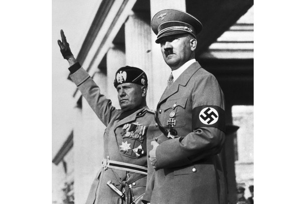 Benito Mussolini and Adolf Hitler watch a Nazi parade staged for the Italian dictators's visit to Germany. Image thought to date from 1937. (Photo by Bettmann via Getty Images)