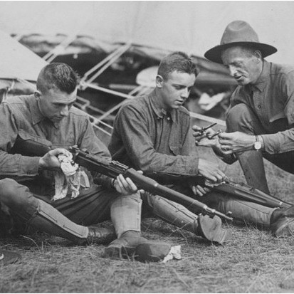 A US soldier teaching two junior 'rookie' recruits how to clean a gun during the First World War. (Photo by Paul Thompson/FPG/Getty Images)