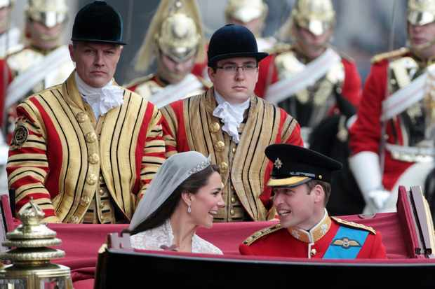 Britain's Prince William and Kate, Duchess of Cambridge, make the journey by carriage procession to Buckingham Palace following their wedding ceremony on April 29, 2011 in London. (Image by Matt Cardy/AFP/Getty Images)