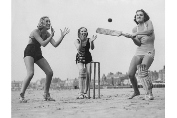 Three girls enjoy a game of cricket on the beach in 1937. (Credit: Fox Photos/Getty Images)