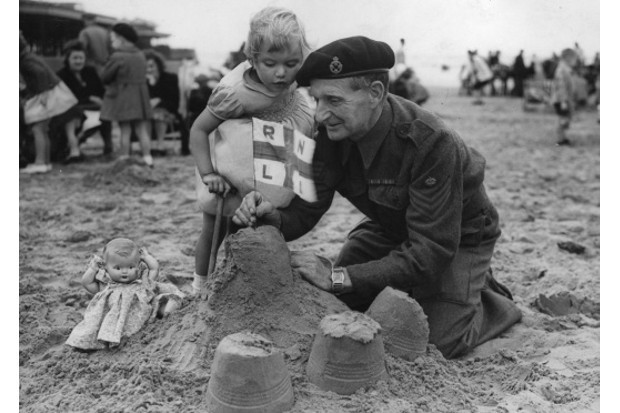 A staff sergeant makes sandcastles for his granddaughter at Blackpool beach while on leave in 1943. (Credit: George W Hales/Fox Photos/Getty Images)