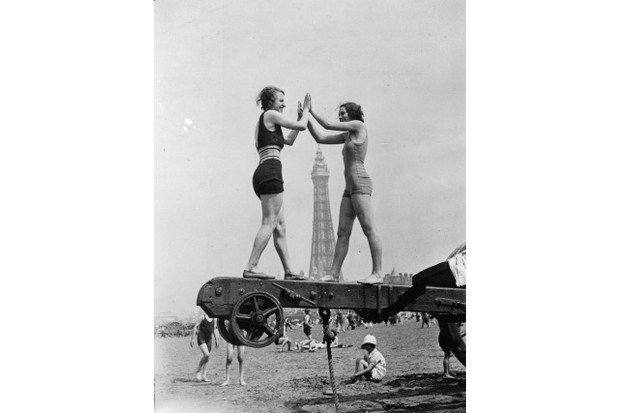 Two holidaymakers enjoy the heatwave on the beach at Blackpool in July 1934. (Credit: E Dean/Topical Press Agency/Getty Images)