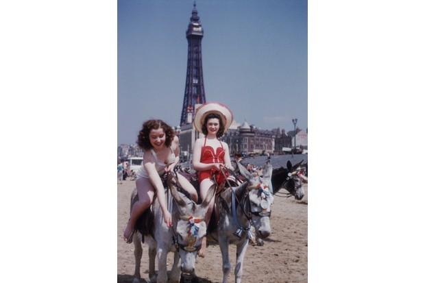 Two holidaymakers enjoy a donkey ride on the beach in c1954. (Credit: John Chillingworth/Picture Post/Getty Images)