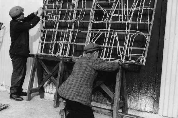 1935:  Two men making a fireworks set piece with the slogan 'God Save The King' for despatch abroad, for the Silver Jubilee celebrations of King George V.  (Photo by Fox Photos/Getty Images)