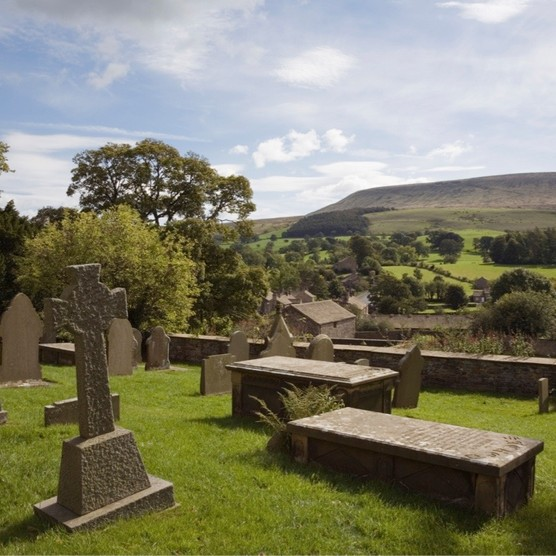 St Leonard's parish church graveyard in Downham, Lancashire, with a view to Pendle Hill. (Photo by PBstock/Alamy Stock Photo)