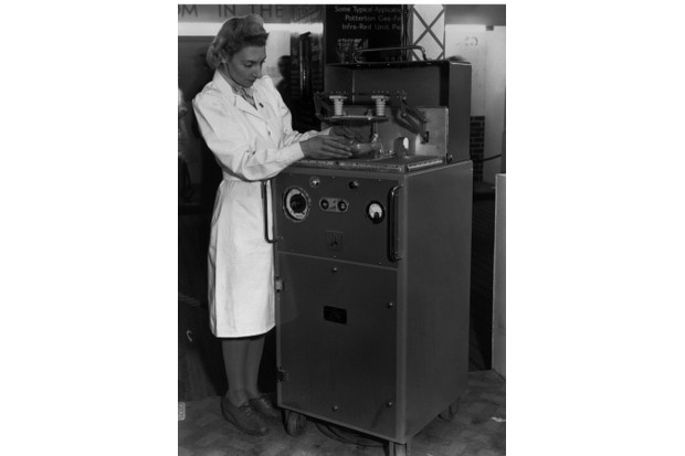 a woman using an early microwave