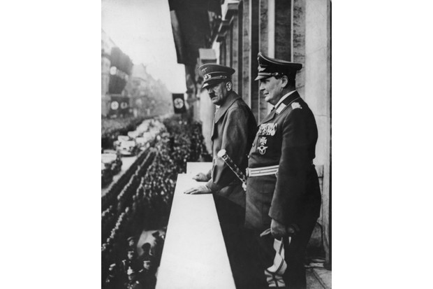 17 March 1938: German Fuhrer Adolf Hitler, left, and Hermann Göring watch a parade honouring Hitler while standing on a balcony at the Chancellory, Berlin, Germany. Hitler had just annexed Austria in the Anschluss. (Photo by Three Lions/Getty Images)
